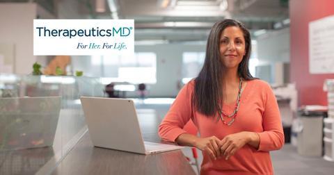 Woman standing near a laptop and TherapeuticsMD logo