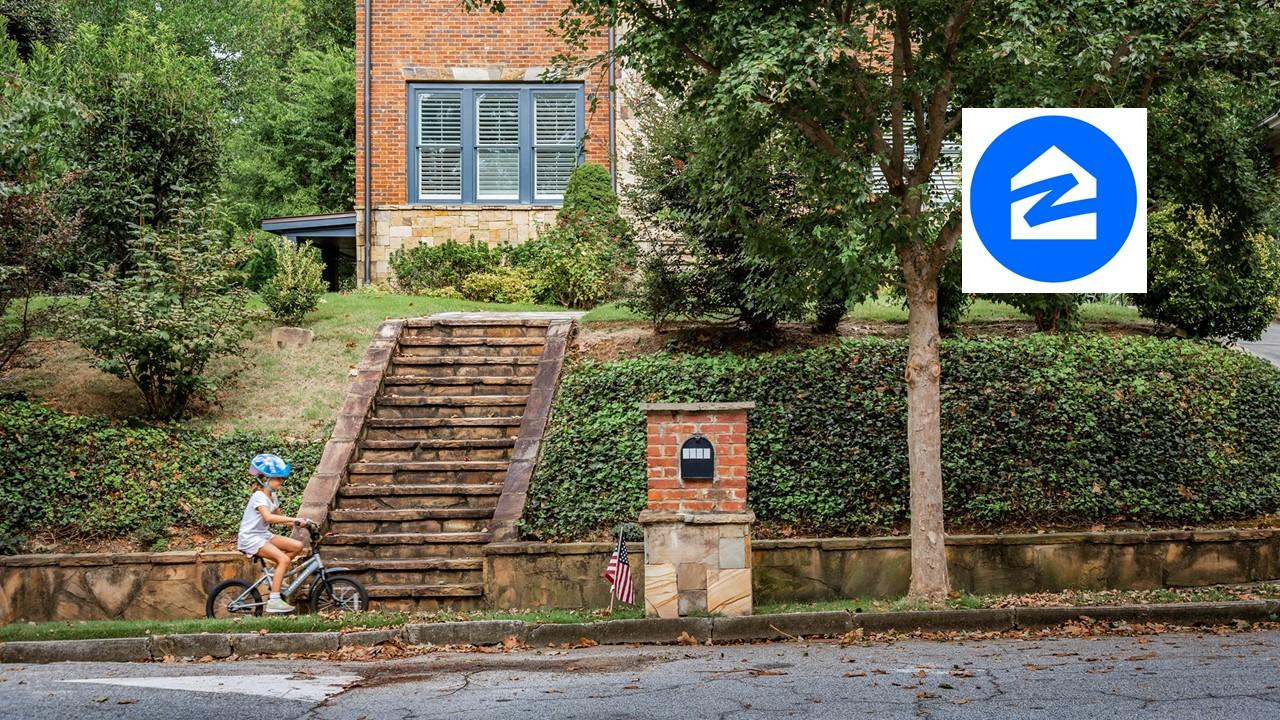 Child riding a bike in front of a home and Zillow logo