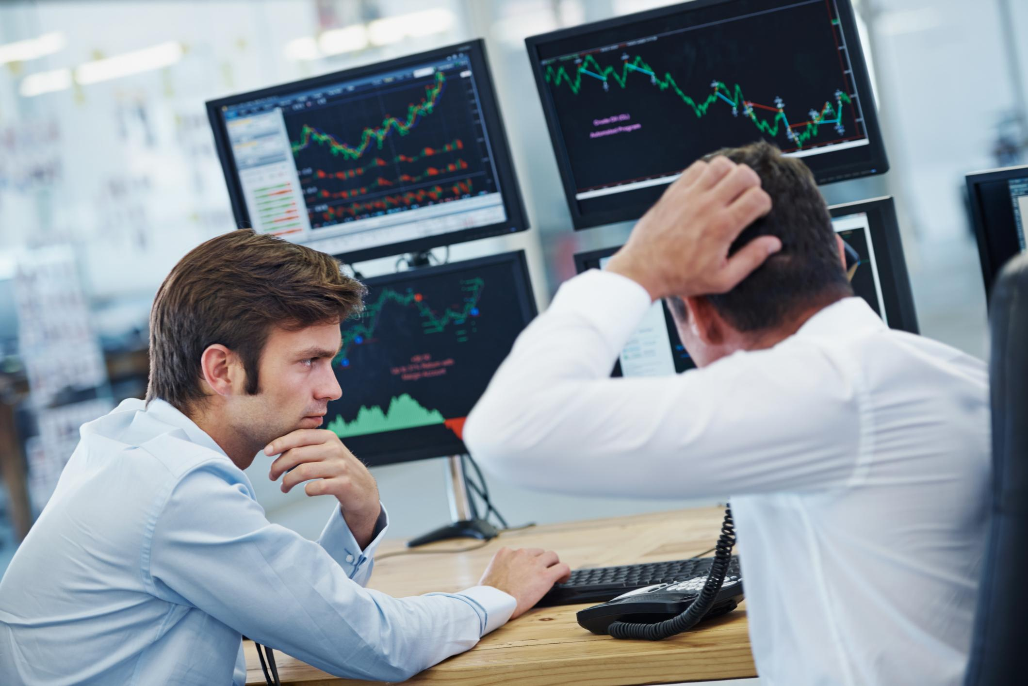Confused investors looking at computer screens