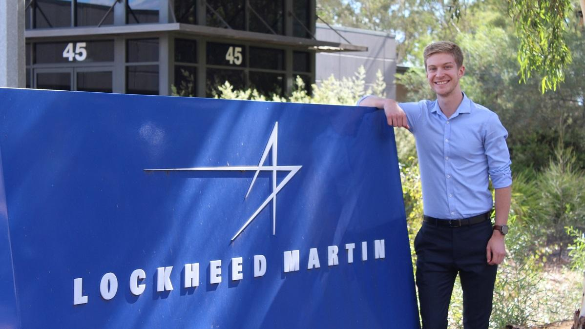 Man standing next to a Lockheed Martin sign