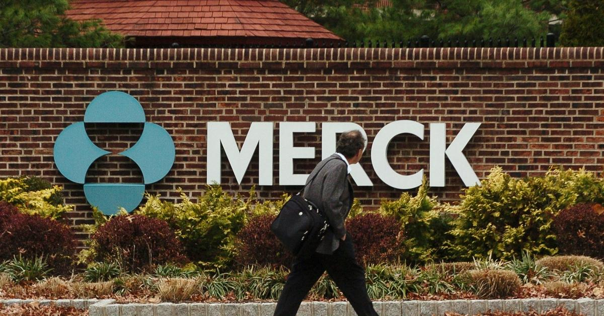 A person walking past the Merck logo on a wall