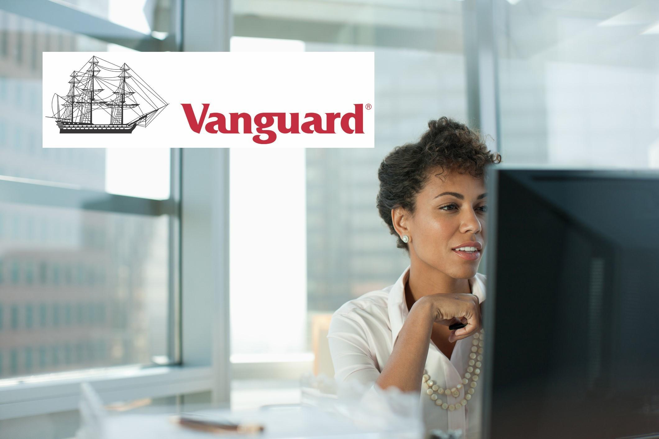 Vanguard logo over investor doing research on VOO VTI ETFs