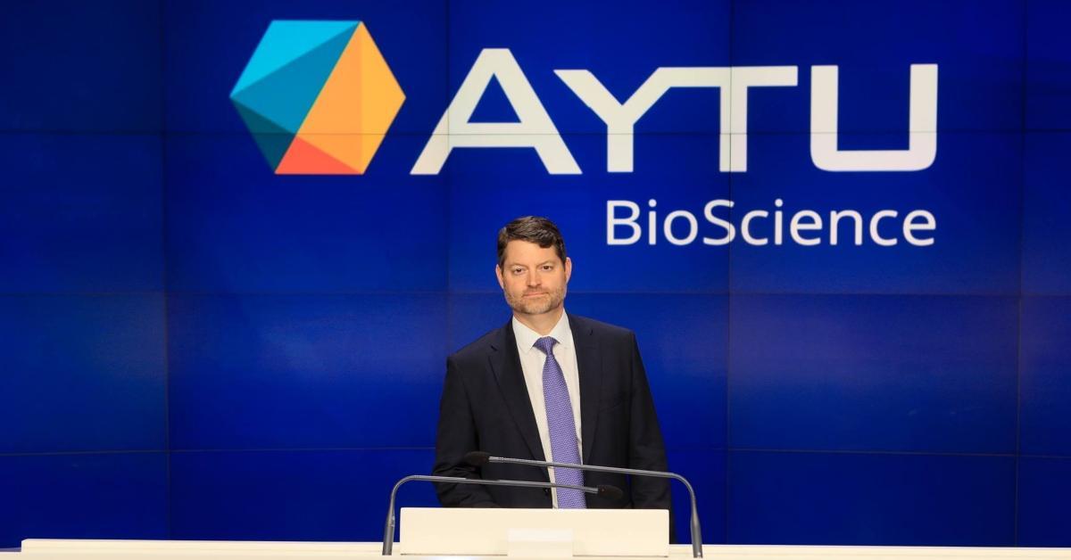 Man standing in front of AYTU BioScience sign