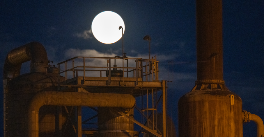 View of the moon above an old power plant