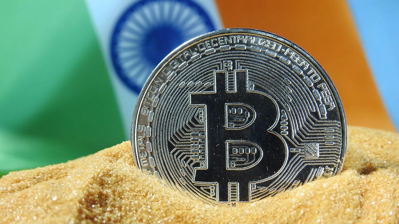 Indian flag behind a bitcoin token in sand