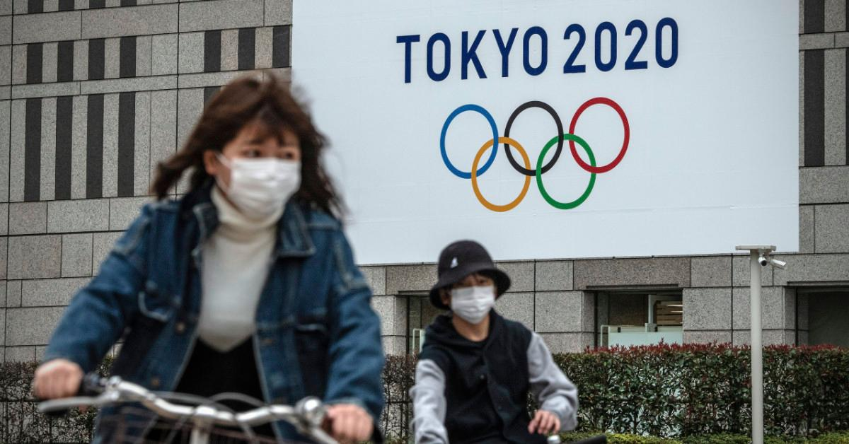People biking in front of a Tokyo 2020 banner