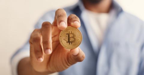 uploads///golden bitcoin in african american man hand closeup