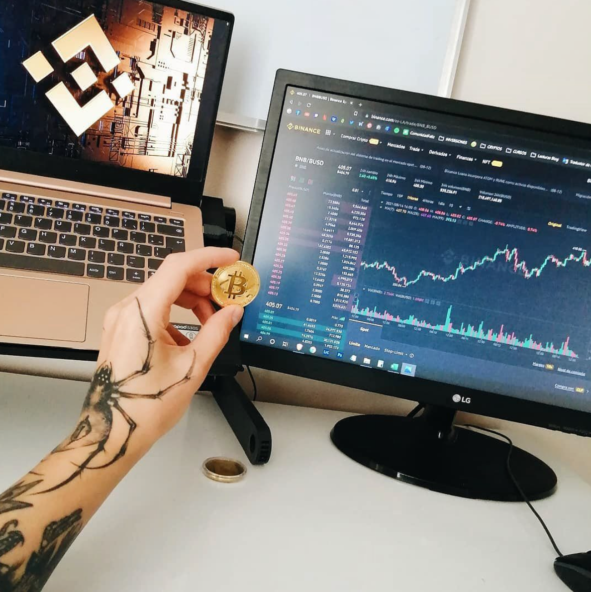 Someone holding a gold Bitcoin in front of a monitor displaying the Binance interface