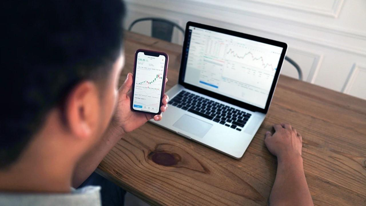 Man looking at stocks on a phone and laptop