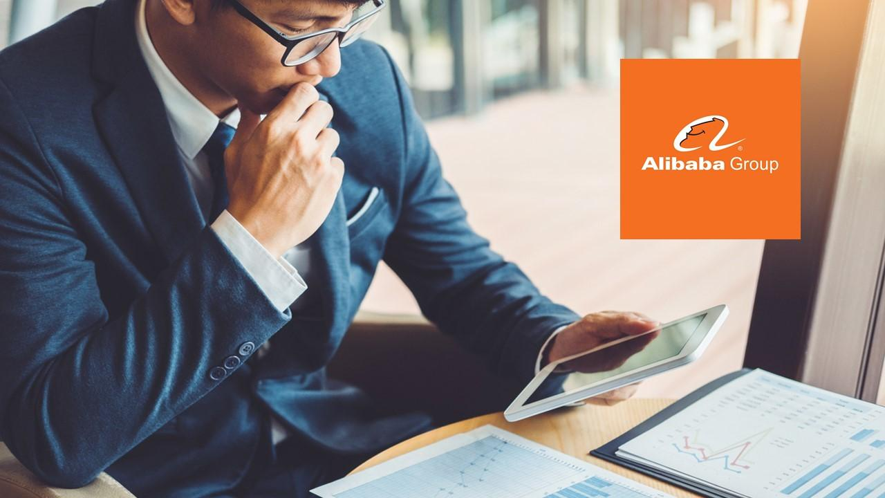 Man looking at data on a tablet and Alibaba logo