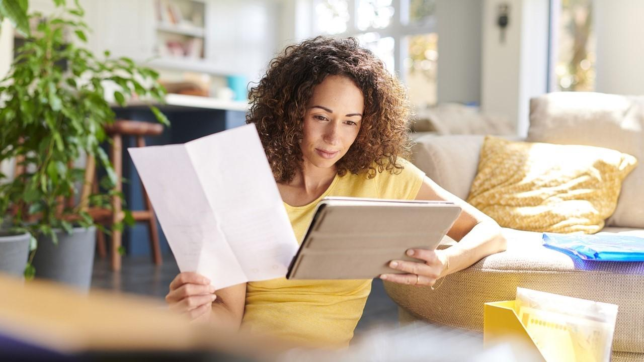 Woman reviewing paperwork and looking on a tablet