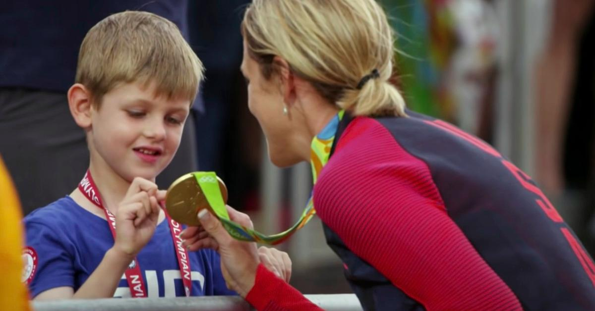 An athlete showing a child her gold medal