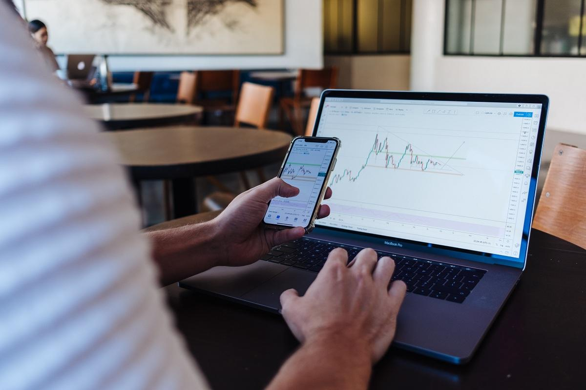 A person checking crypto prices on a phone and laptop