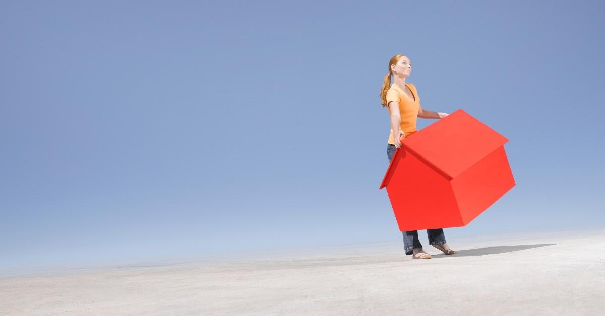 An illustration of a person carrying a red house