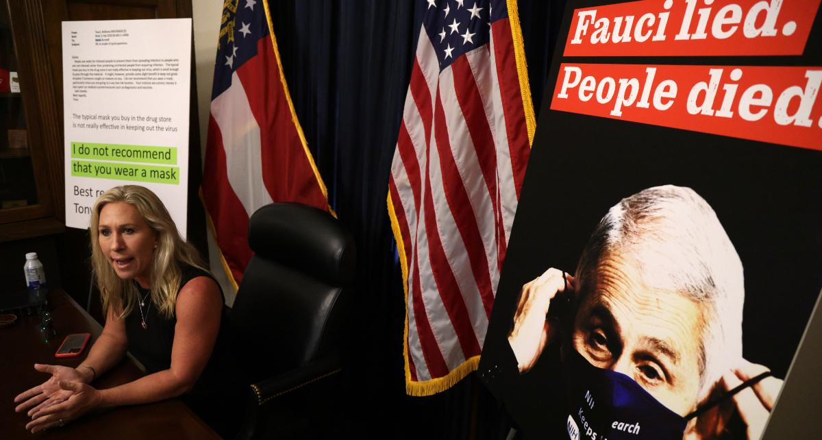 U.S. Rep. Marjorie Taylor Greene with Fauci poster in background