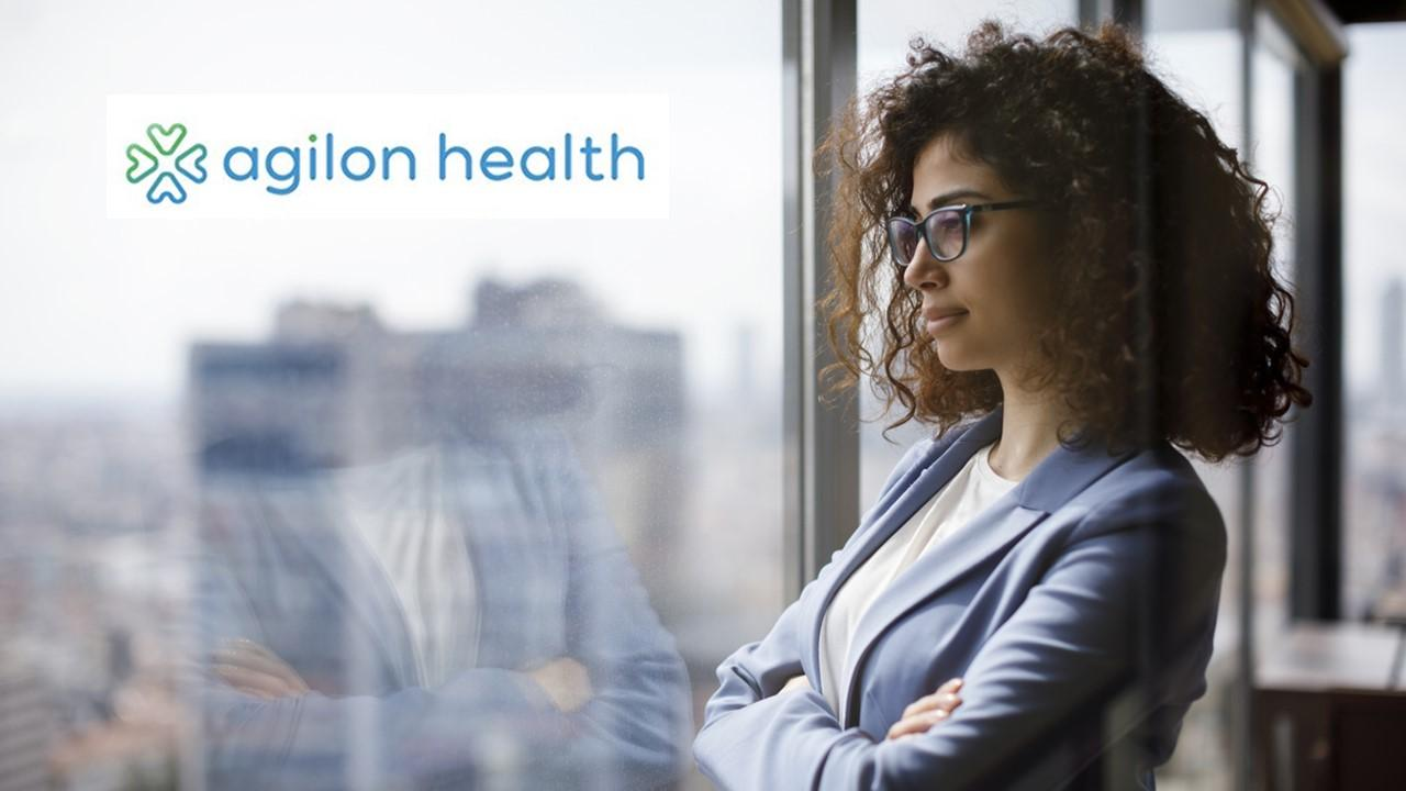 Woman standing at a window and Agilon Health logo