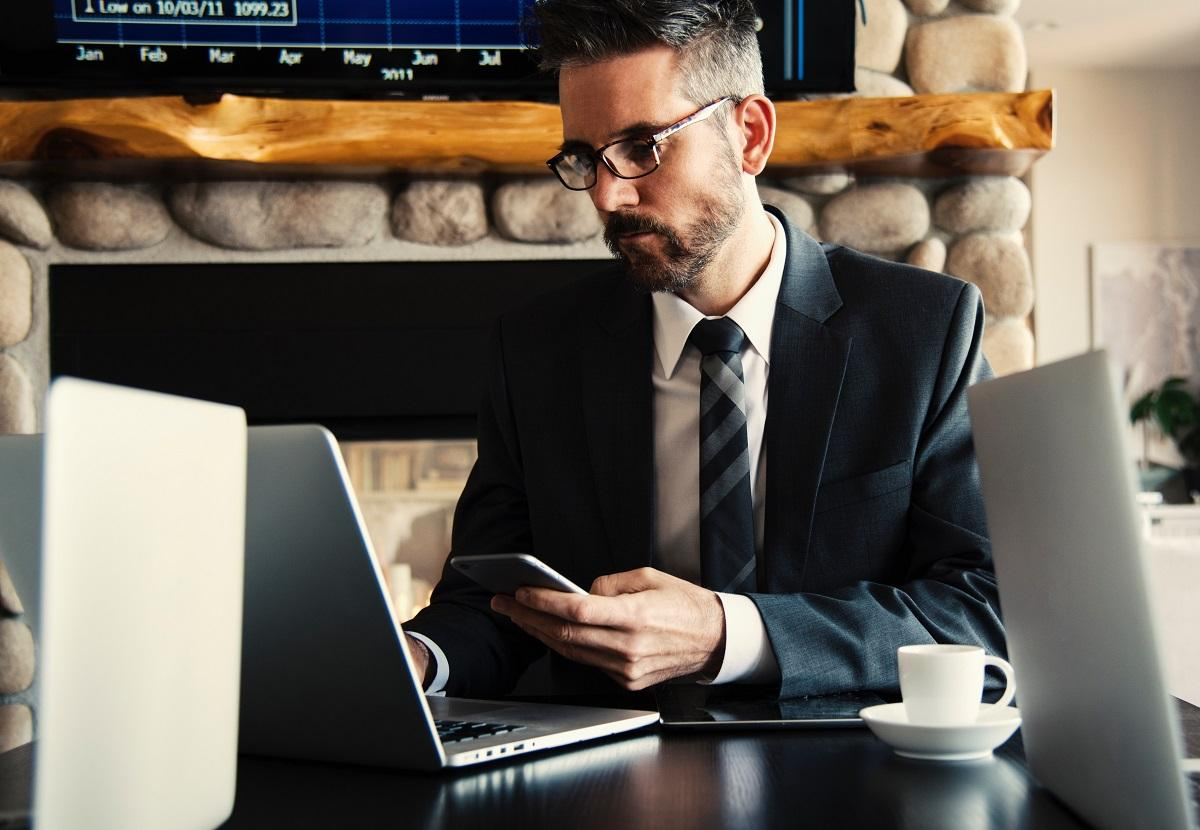 Man holding a phone and looking on a laptop