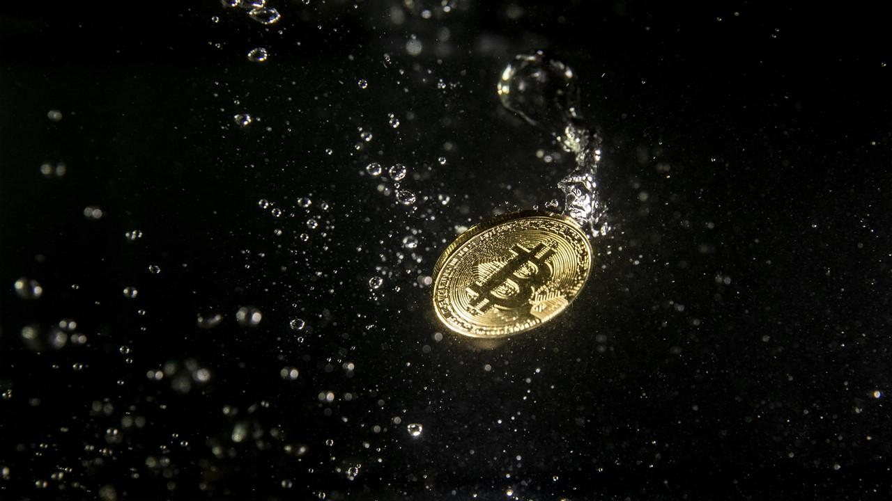 Bitcoin token in water