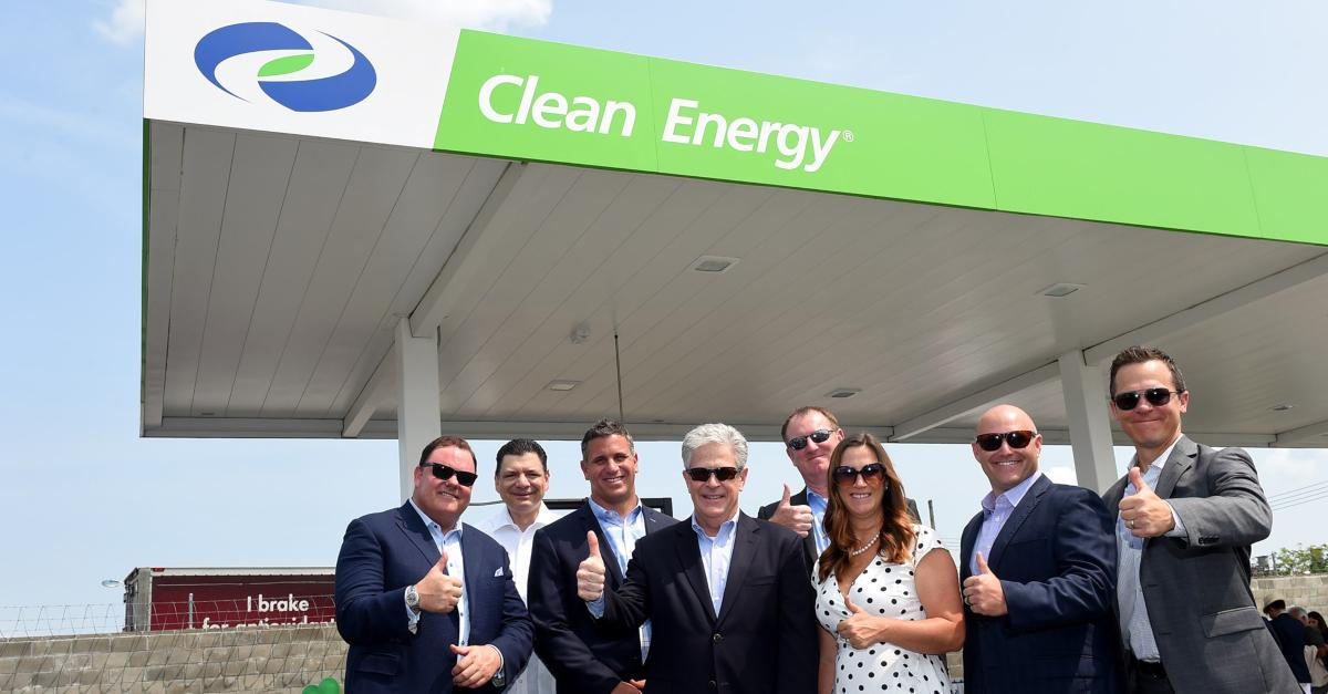 Clean Fuels executives posing in front of a fuel pump