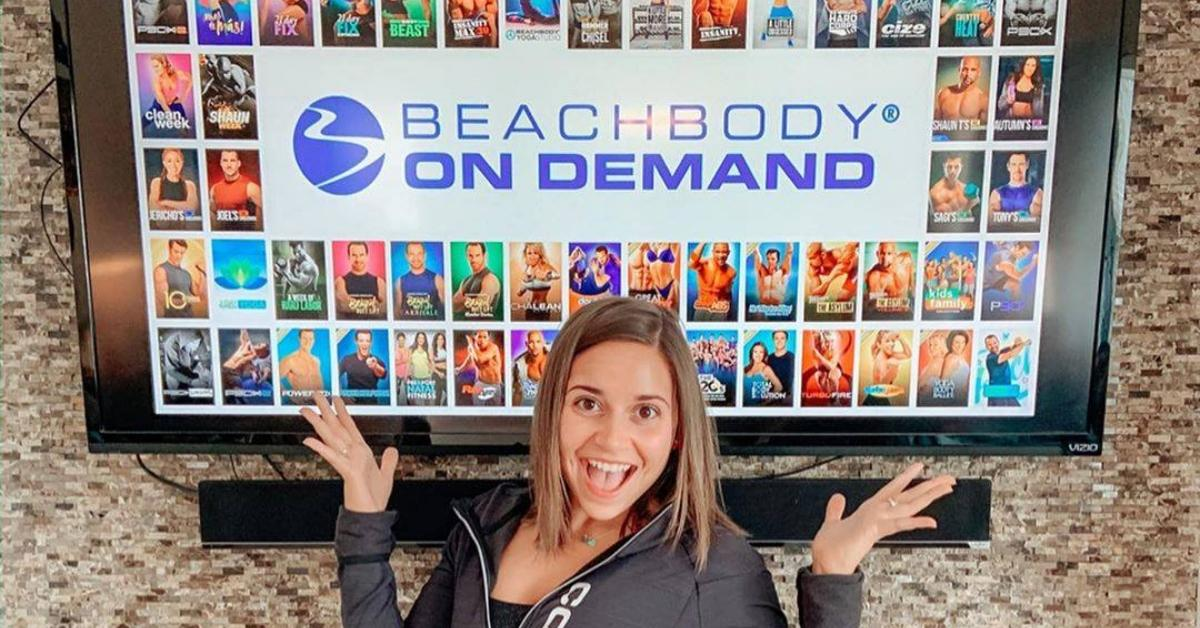 Woman in front of a tv with Beachbody on Demand on the screen