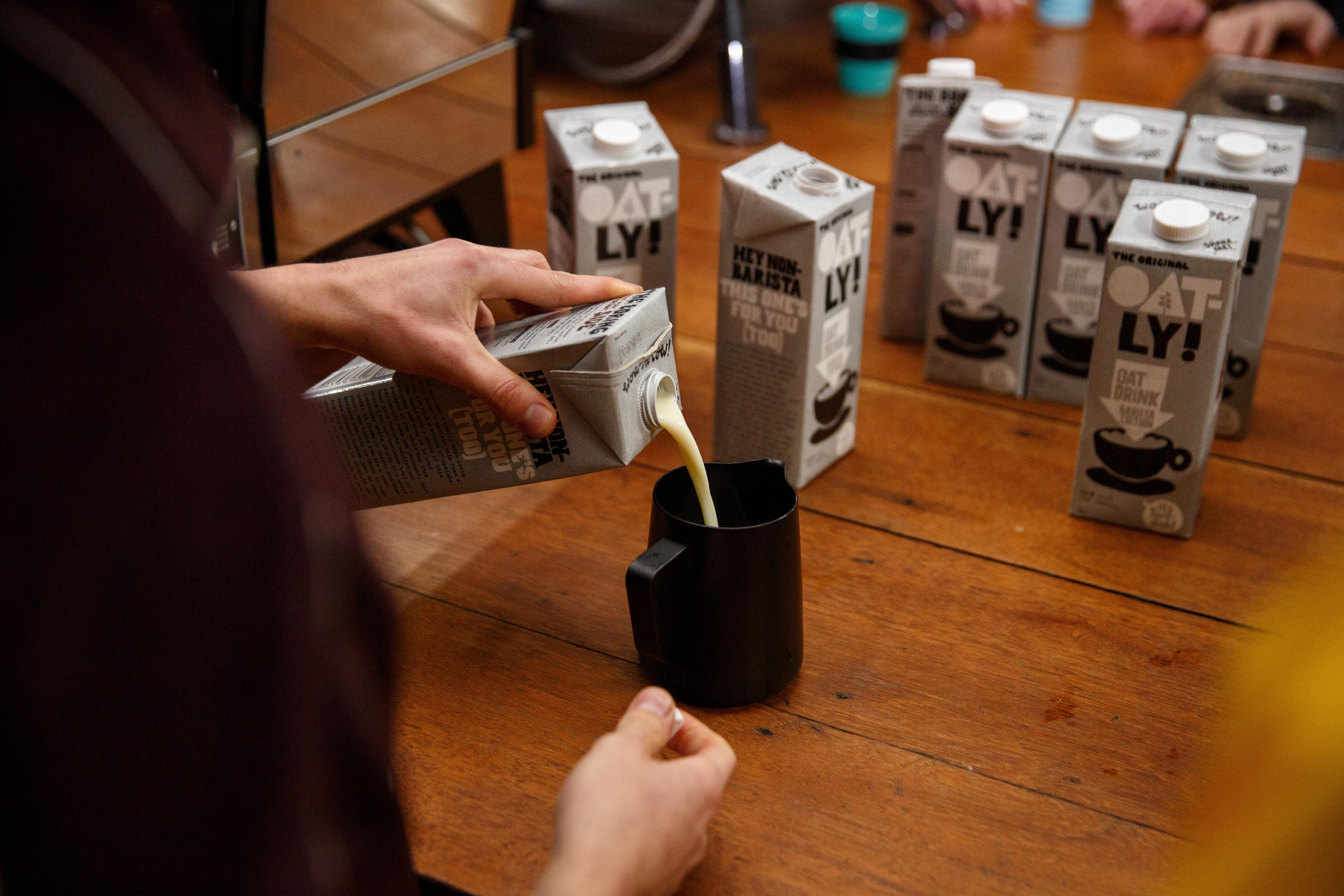 Person pouring Oatly milk into a cup